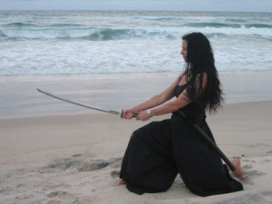 Kim Falconer training with the katana on the beach